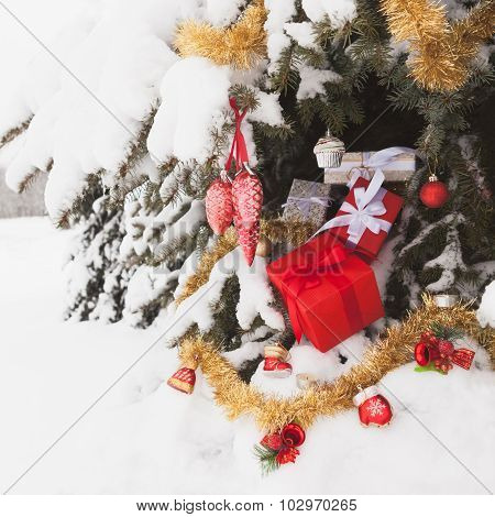 Christmas square background with fir, gift boxes and decorations on the snow