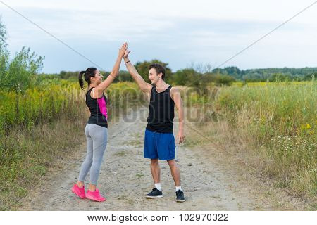 Male And Female Making High Five In Countryside