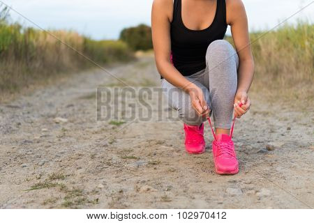 Young Sporty Woman Tying Shoe Laces Outdoors
