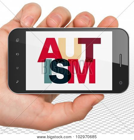 Healthcare concept: Hand Holding Smartphone with Autism on  display