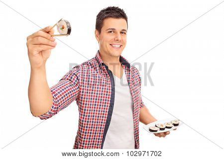 Joyful young man holding a piece of sushi between Chinese sticks and looking at the camera isolated on white background
