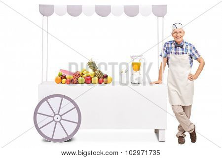 Senior soda jerk standing next to a stall with a juicer and a bunch of fresh fruits on it isolated on white background