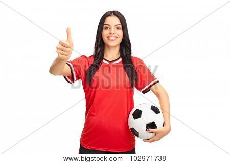 Young female soccer player holding a ball and giving a thumb up isolated on white background