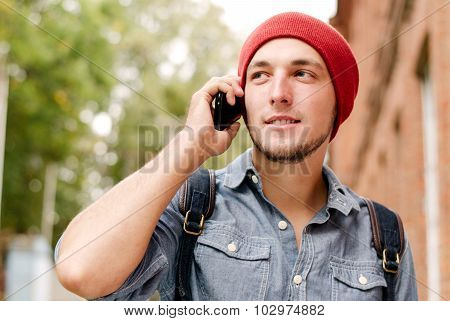 The Young Man With Red Cap Calls On His Cell Phone
