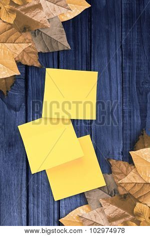 Sticky note against autumn leaves pattern
