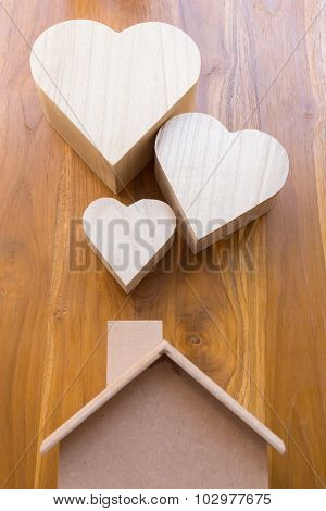 Wooden House And Heart On Brown Wood Background
