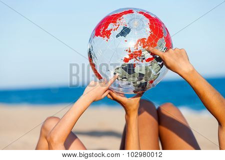 Hands Pointing At Inflatable Earth Ball.