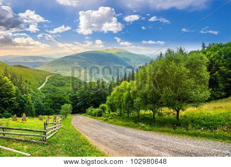 Fence Near Road Down The Hill With  Forest In Mountains At Sunrise