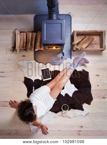 Young woman with cup of coffee sitting home on a cow rug by the fireplace. Fall winter relaxing and leisure concept.