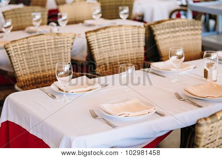The interior of summer cafe - sheltered tables with white tablec