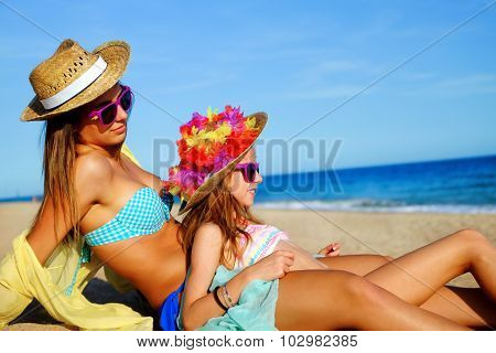Young Mother Sitting With Daughter On Beach.