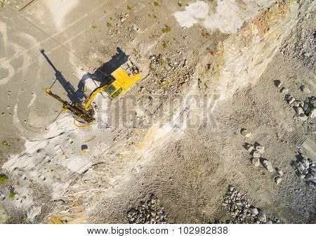 Aerial view of a drilling machine in the mine. Industrial background from landscape after mining.