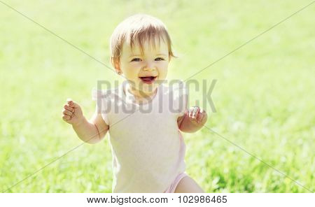 Cheerful Smiling Baby On The Grass In Sunny Summer Day
