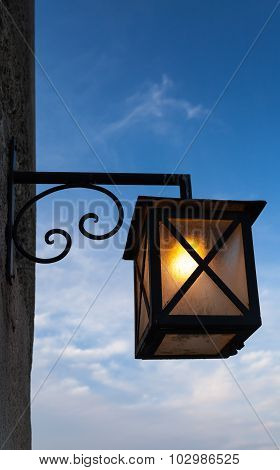 Ancient Street Lamp Mounted On Stone Wall