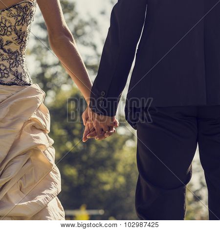 View From Behind Of Newlywed Couple Holding Hands