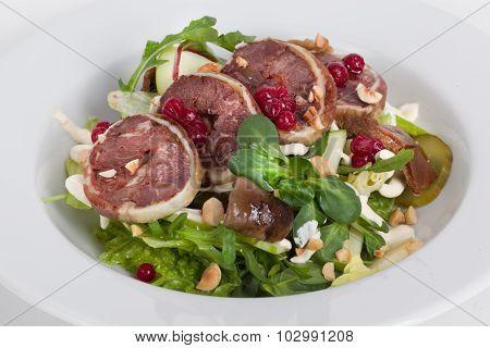 venison salad, watercress, hazelnuts, arugula on a plate close-up food cranberries