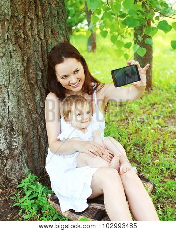 Happy Smiling Mom And Baby Taking Self-portrait On Smartphone Sitting On Grass In Summer Park