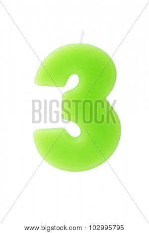 Green birthday candle in the form of the number three on white background