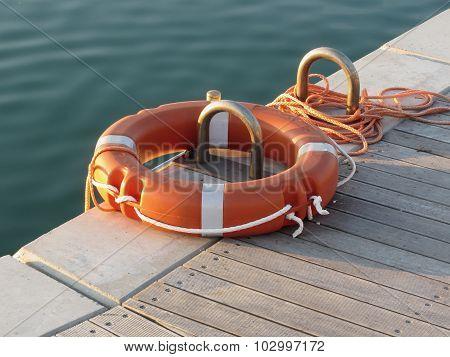Orange Life Buoy On Wooden Pier In The Harbor In Marina Di Pisa, Tuscany, Italy