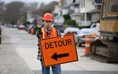 image of road construction  - road construction worker holding a detour sign and gesturing to stop - JPG