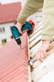 stock photo of roof tile  - Hands of builder worker at roofing works on tiling with screwdriver - JPG