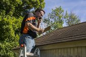 Постер, плакат: Contractor On Ladder Figuring Hail Damage Reairs To Roof