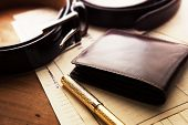 Documents, pen, belt and a leather wallet on a wooden desk. hotel table or gentlemans desk. shallow poster