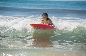 stock photo of boogie board  - Girl child floating on green ocean as she rides the boogie board - JPG