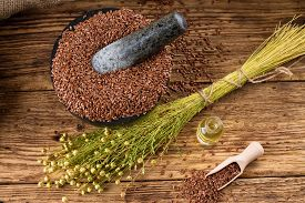 stock photo of flax seed oil  - Horizontal photo with a bunch of flax plants with dried blooms bonded by natural cord placed on old wooden board and with burlap around which is near to bottle with flax oil and heap of flax seeds - JPG