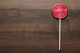 foto of lollipops  - red sugar lollipop on the wooden table - JPG