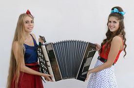 image of accordion  - two smiling girls holding old accordion - JPG