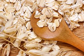 foto of oats  - Rolled oats and oat ears of grain on a wooden table close - JPG