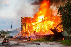 stock photo of firemen  - Fireman extinguishes a burning old wooden residential house - JPG