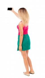 image of jeans skirt  - back view of standing young beautiful  woman  in vest and using a mobile phone - JPG