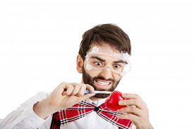 pic of scalpel  - Determined man wearing suspenders cutting heart model with scalpel - JPG