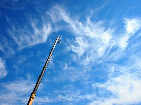 pic of boom-truck  - The boom of the crane on a diagonal against a blue sky with white cirrus clouds - JPG