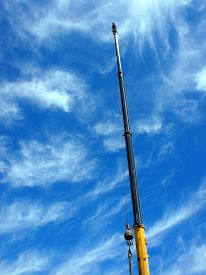 picture of boom-truck  - Upward view on the boom of a crane against the blue sky with white cirrus clouds - JPG