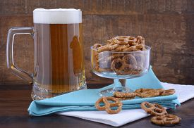 image of stein  - Glass of beer in stein with mini pretzels on pale blue napkin on wood background - JPG