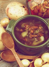 pic of chanterelle mushroom  - Homemade Vegetarian Soup with Chanterelle Mushrooms in Green Pot and Raw Ingredients closeup Rustic Wooden background - JPG