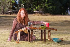 picture of sabbatical  - Caucasian priestess in outdoor pagan ritual with altar - JPG