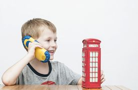 picture of phone-booth  - Little cheerful boy talking on the phone and vintage british red telephone booth - JPG