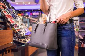 stock photo of shoplifting  - Young woman is stealing goods in a shop - JPG