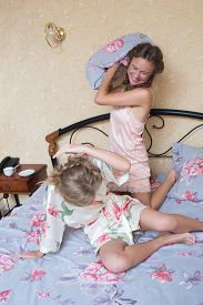 image of pillow-fight  - Two beautiful young woman fighting with pillows in bed - JPG