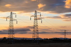 stock photo of electricity pylon  - Sun setting behind a row of electricity pylons - JPG