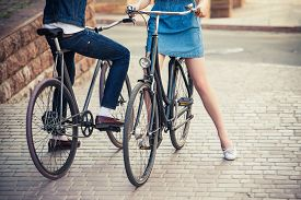 pic of opposites  - The legs of young couple sitting on bicycles opposite the city - JPG