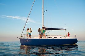 stock photo of yacht  - Young people is resting on a sailing yacht at sea. Weekend on a yacht. Yachting. Cruise on a yacht on the ocean. Guys and girls are traveling on a yacht. Youth party on a yacht. ** Note: Soft Focus at 100%, best at smaller sizes - JPG
