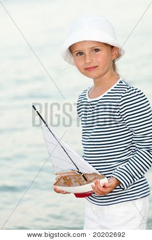 Summer vacation - little girl with yacht model at the beach portrait