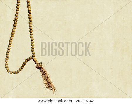 simple illustration featuring prayer beads against simple light brown background