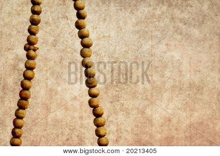close-up of prayer beads on a simple light brown background and plenty of space for text