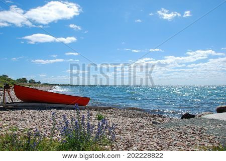 Beautiful coastline at the swedish island Oland with a landed small red boat